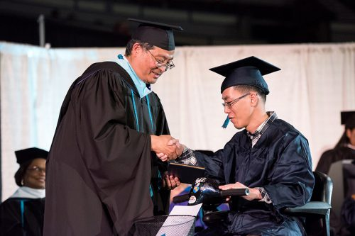 Student in electric scooter receiving diploma