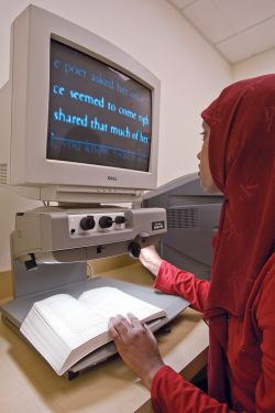 student reading enlarged text on display reader