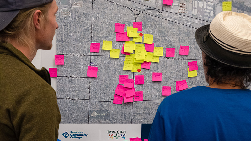 People looking at sticky notes with messages on a map of northeast Portland