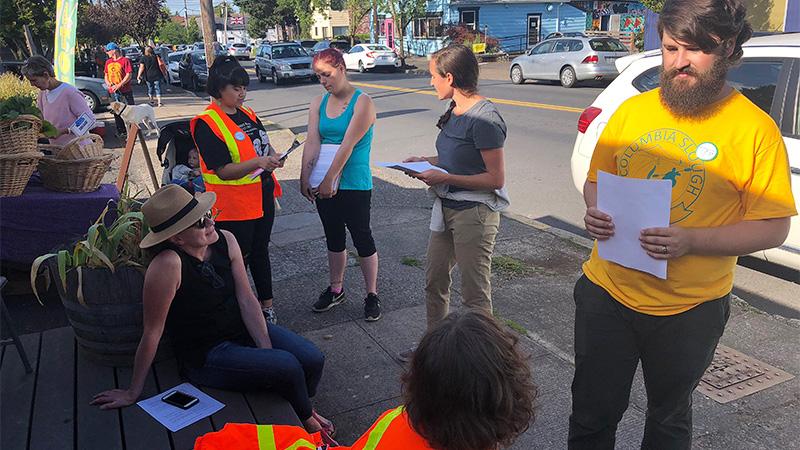 Volunteers holding surveys and talking to people on the sidewalk