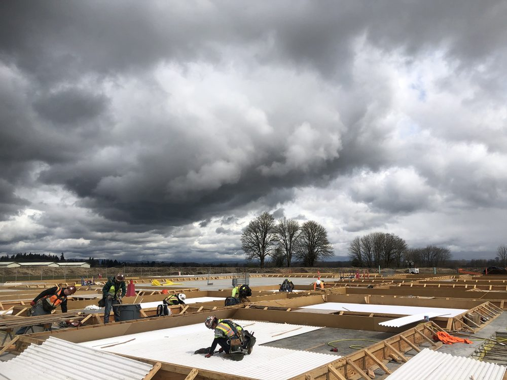 People working on the construction site under dramatic gray clouds