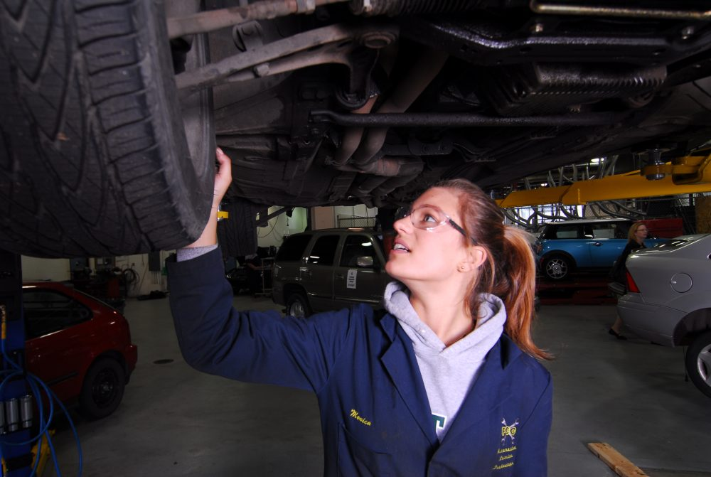Automotive Services student looking under a car