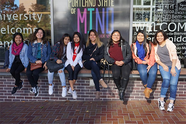 Students sitting on a brick wall in a group