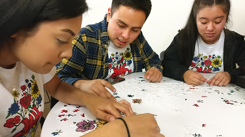CAMP students doing a jigsaw puzzle together