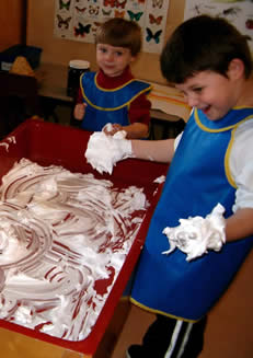 Kids playing with shaving cream on a table