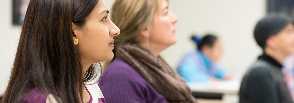 Three female clients look ahead while learning about individual professional career skills in a CLIMB classroom