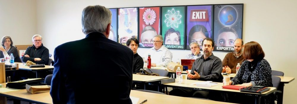 SBDC classroom with five professionals discussing global trade.