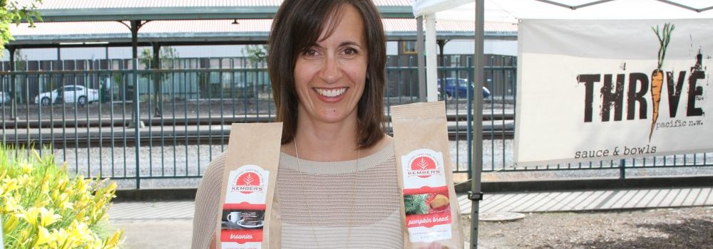 Marilyn Kember, owner at Kember's Gluten Free, smiles while holding up two bags of her baked goods recipe mixes, one in each hand