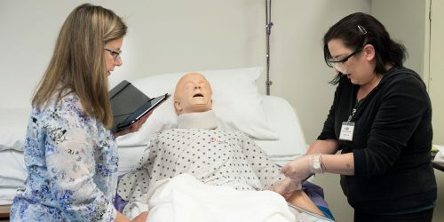 An instructor coaches a female student as she practices entry level CNA skills on healthcare mannequin in bed