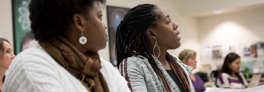 Two female students listen intently in a professional development course.