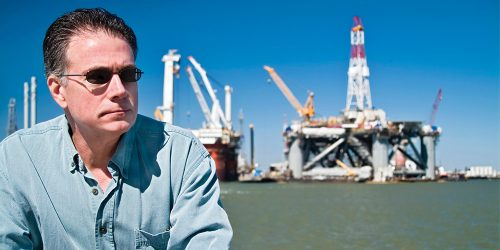 Man sitting in front of ocean with industrial rig in background