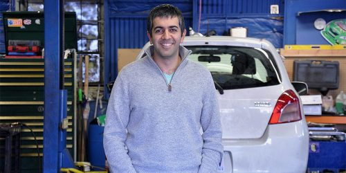 SBDC Client Farhad Ghafarzade standing in front of cars at Green Drop Garage