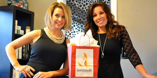 Bombshellers business women smiling with a gift bag of their product