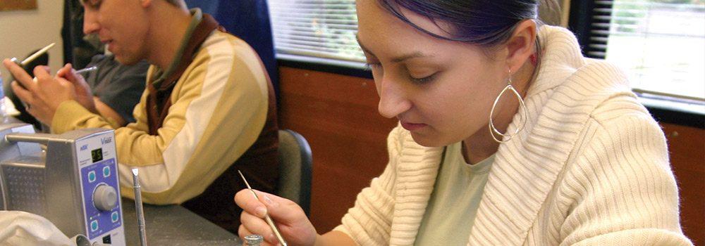Dental Heath Technician works on tooth mold