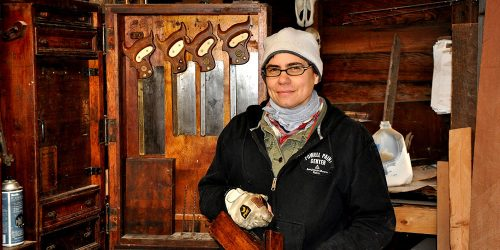 Amy at Oculus carpentry, wearing hat and gloves, stands in front of saws and other woodworking tools