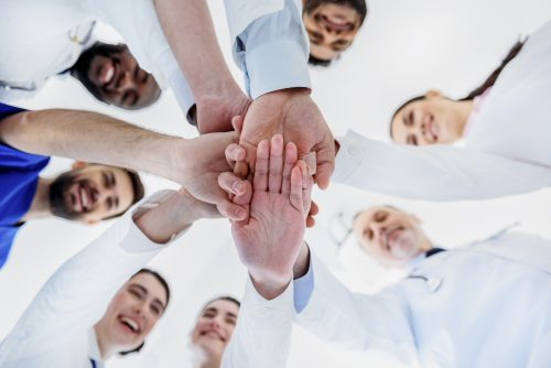 Low angle of joyful doctors joining hands together and smiling. Focus on their palms
