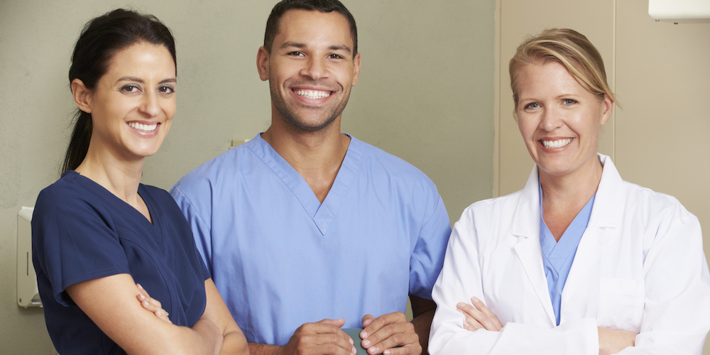 Portrait Of Dentist And Dental Nurses In Surgery garb