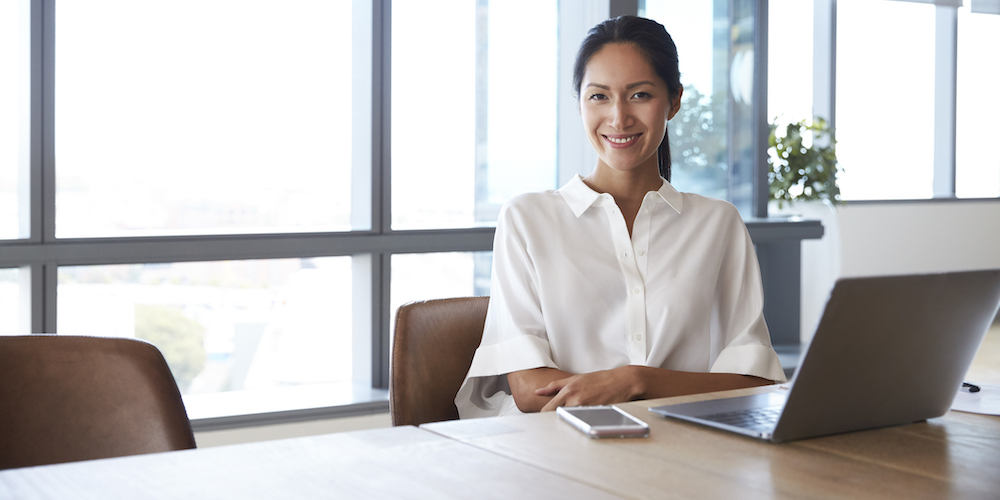 confident female asian student in front of computer
