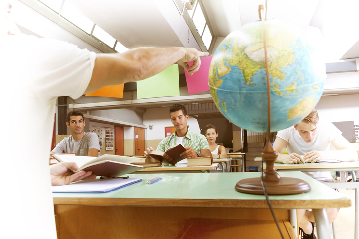 group of students follow the lesson in a classroom with a globe in the photo