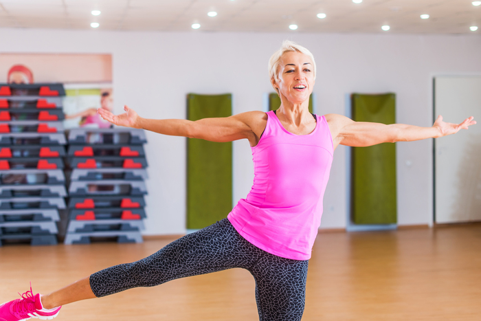 Cheerful muscular blonde middle-aged fitness trainer holding balance on one leg with arms sideward while performing step aerobics dance exercise in gym.