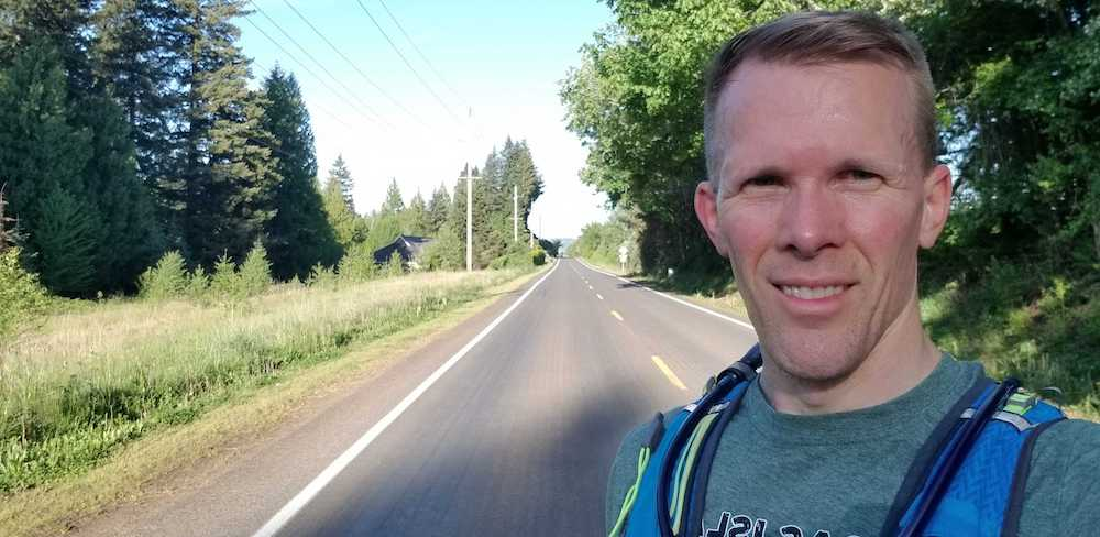 Instructor Evan Jensen running on backroad in Oregon and posing for a selfie