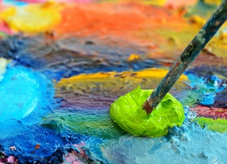 Picture of palette with mixture of paint colors and paintbrush.
