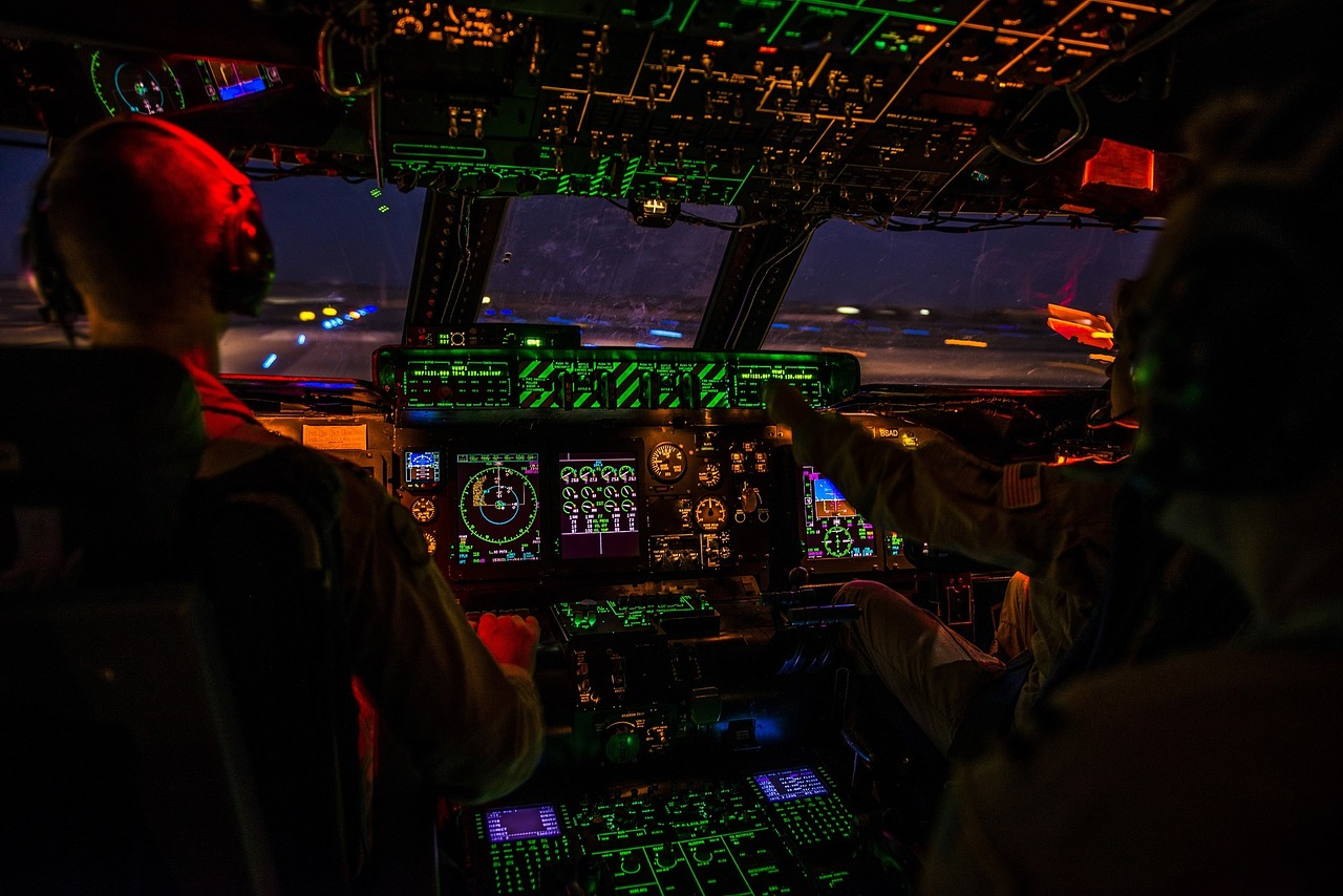 View from the cockpit of a plane at night. The instrumentation is all lit up.