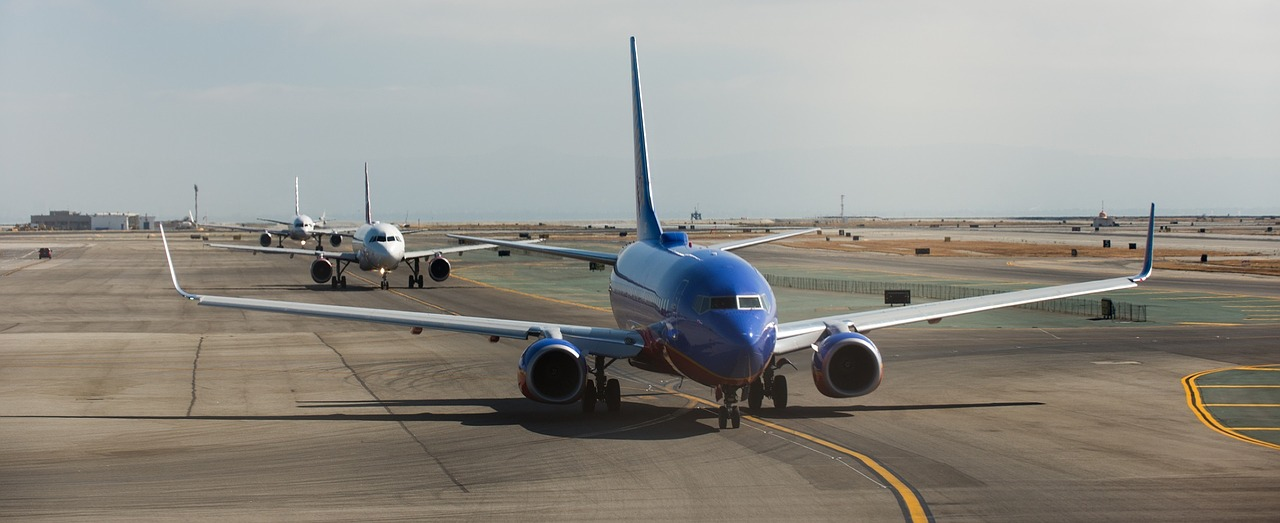 several airplanes queued up for takeoff on a runway.