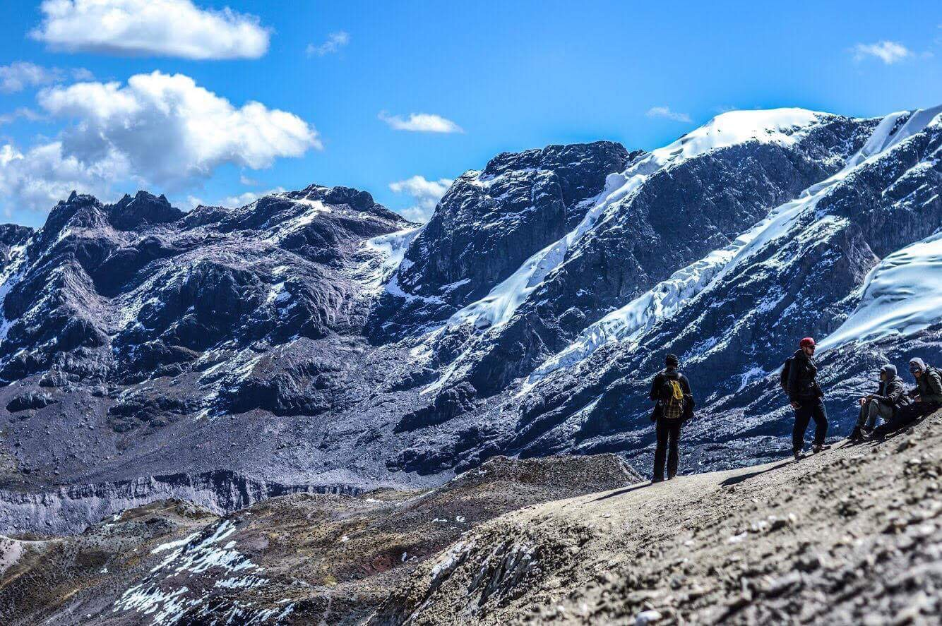 Photo of rocky mountains with some snow, hikers standing in the foreground.