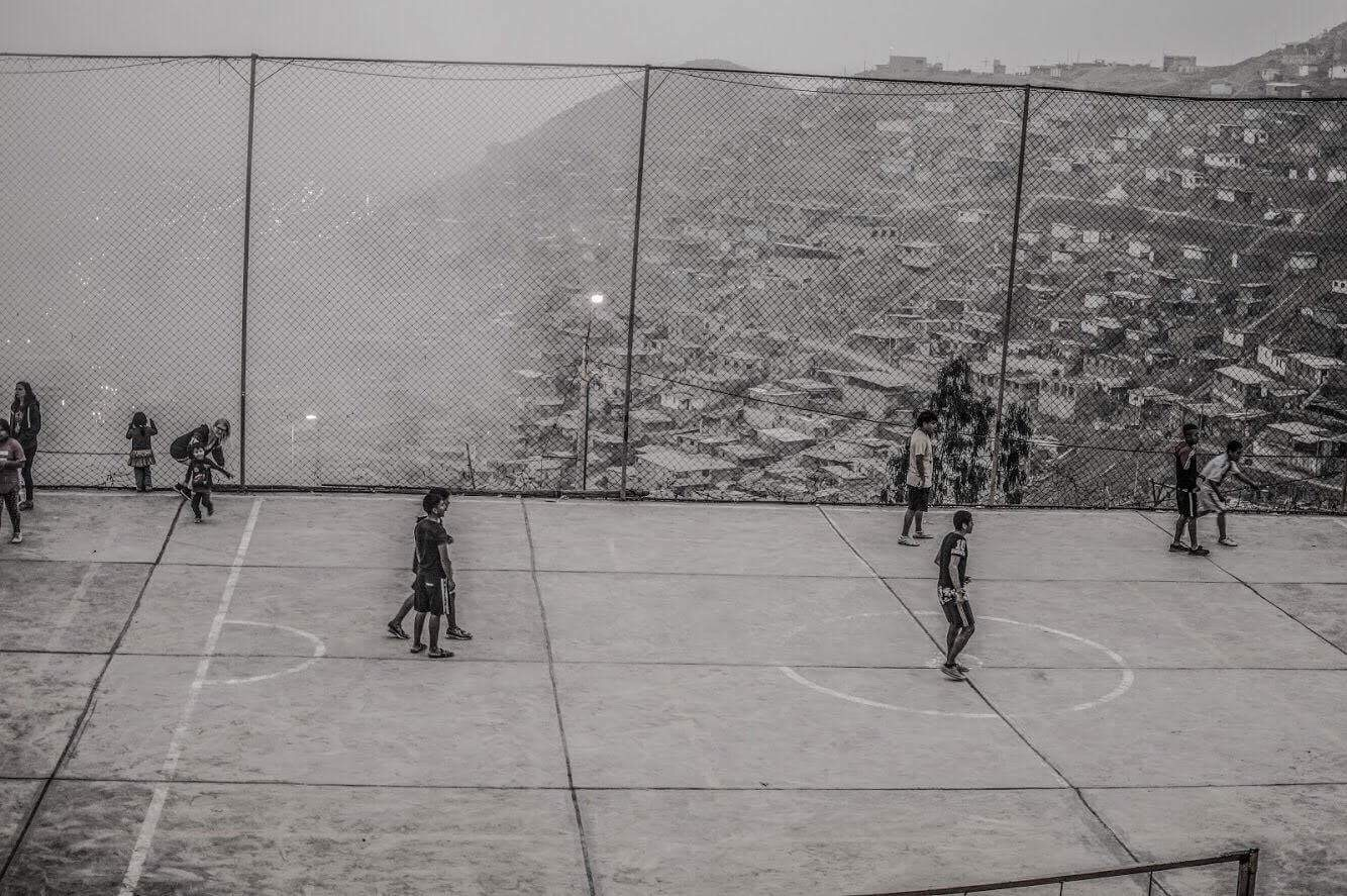 A black and white photo of children playing soccer on a court in front of city buildings covering a hillside.