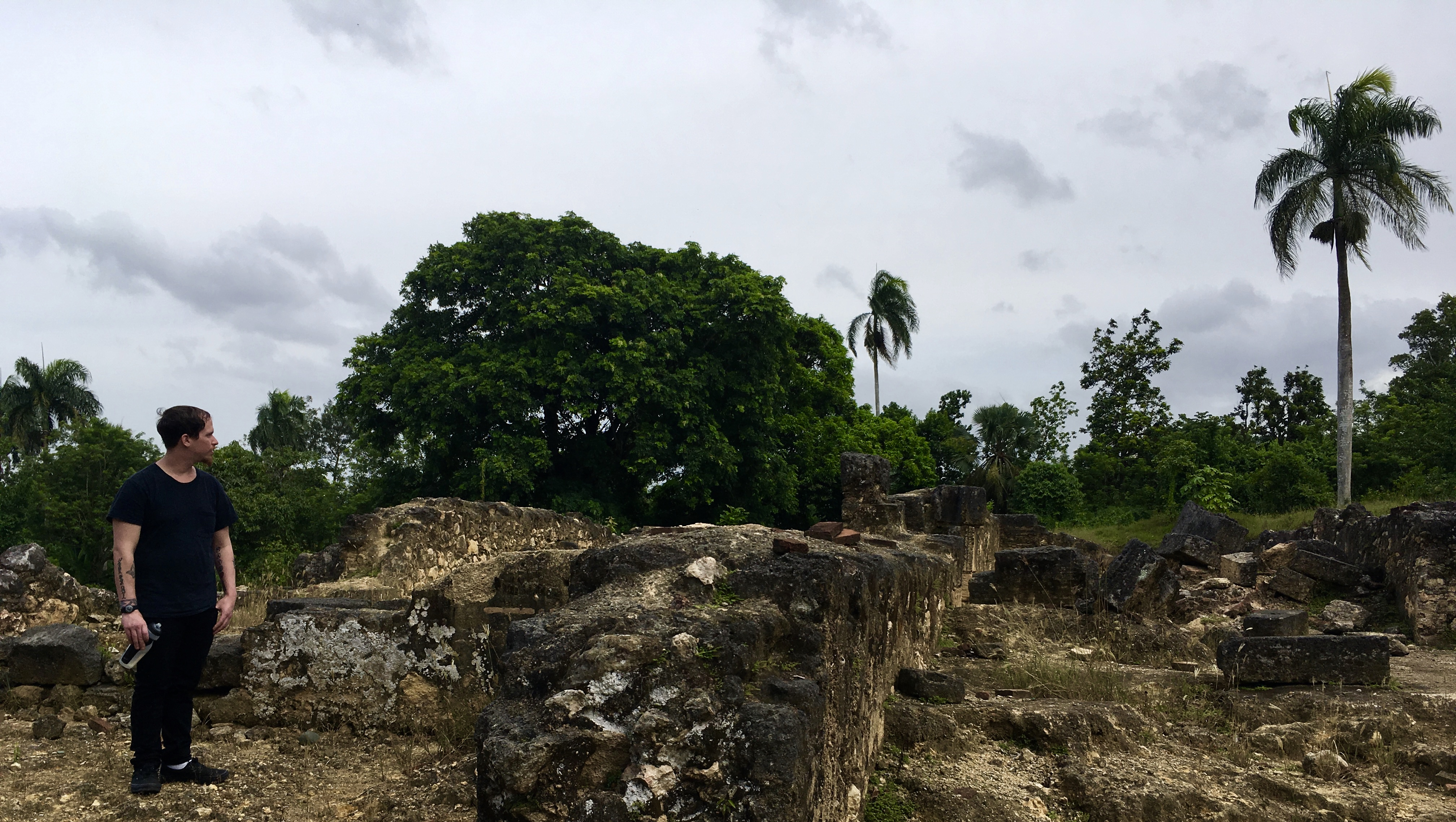 Photo of a student standing next to ruins with trees in the background.