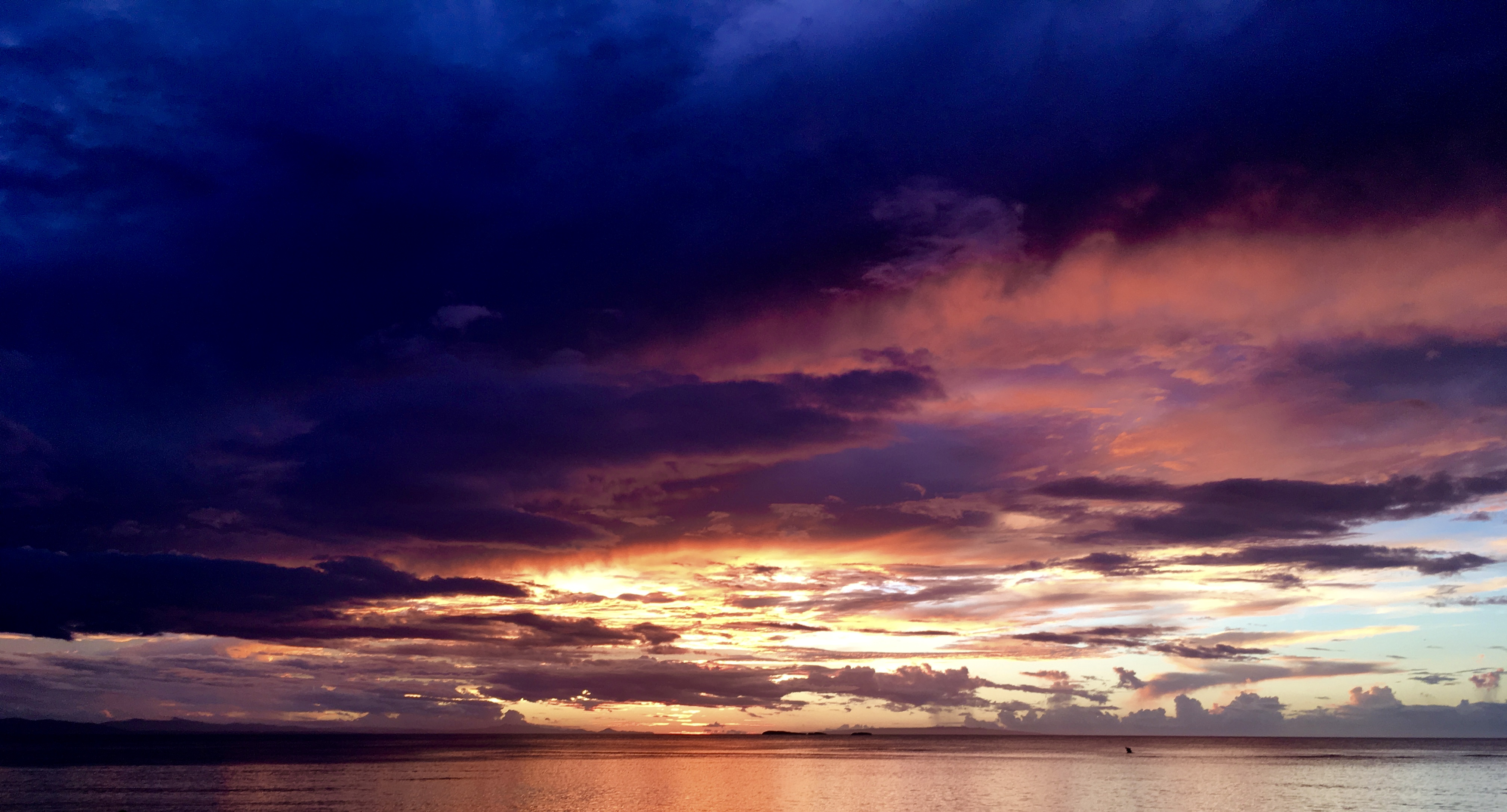 A photo of a sunset with dark purple clouds on top, leading into yellow and orange clouds by the sea.