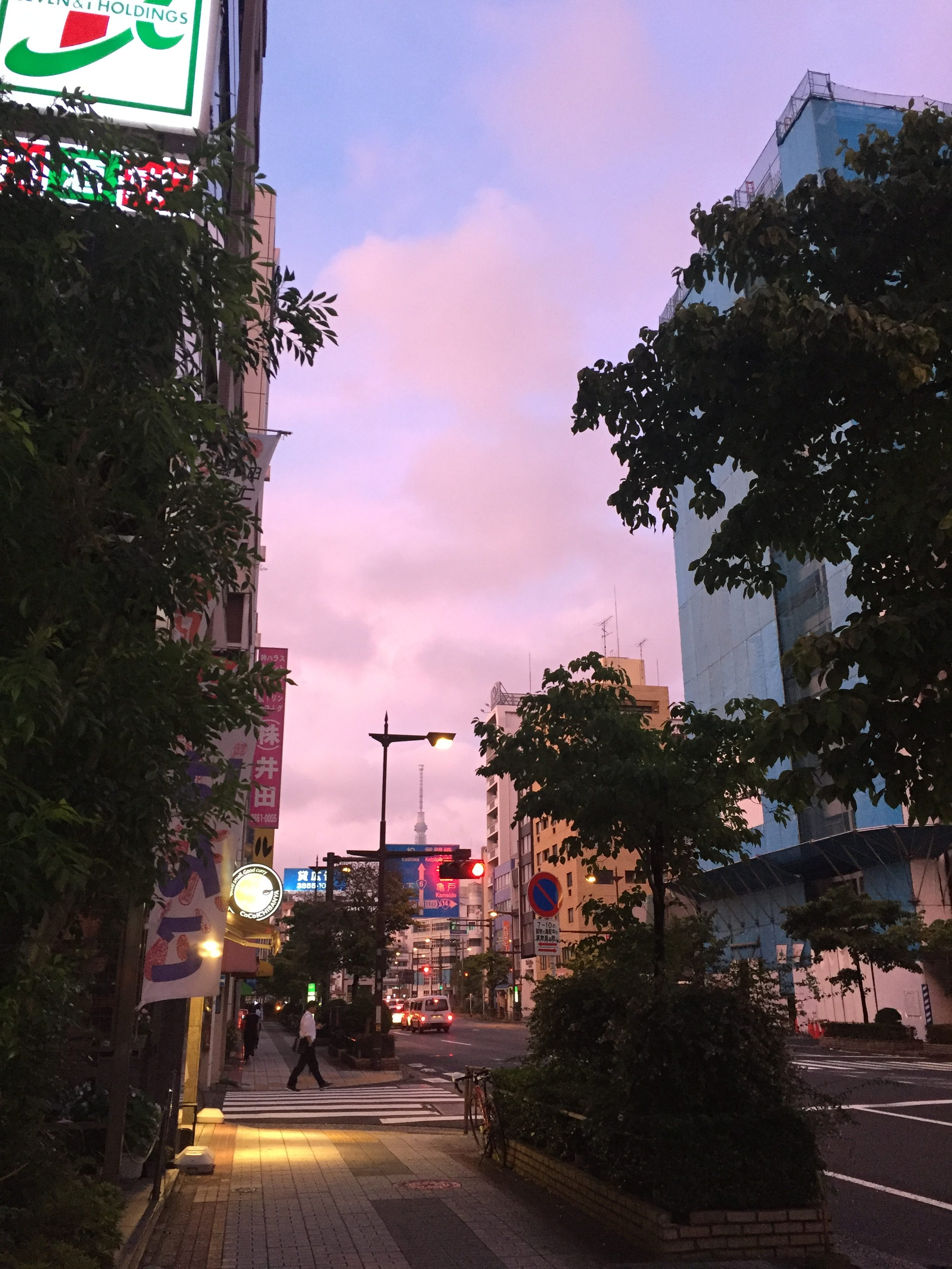 A photo of a city street at sunrise, with a light pink and blue sky.