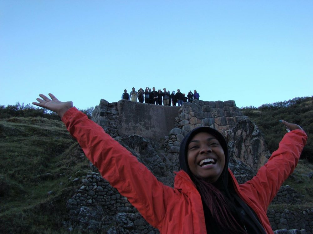Photo of Sade Mitchell in front of a rock wall, with her fellow program participants standing on top.