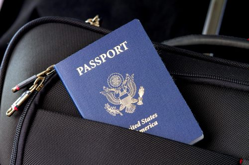Blue US passport sticking out of a suitcase pocket