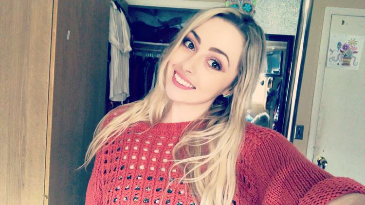 Cailyn Higgins, 2018-19 EAO Peer Mentor, young female with brown eyes, blonde hair, wearing a red pullover and small green triangle earrings, standing in front of her closet and smiling.