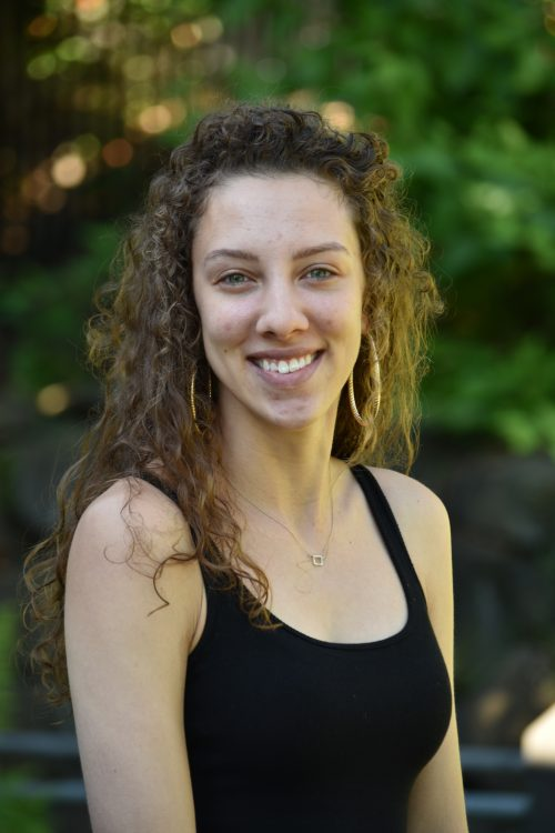 Emory Neer, 2018-19 EAO Peer Mentor, portrait photo of female with curly hair, wearing a black tank top, large golden earrings, and a necklace.