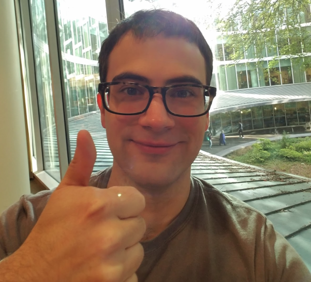 Rico Ruff, 2018-19 Education Abroad Office Peer Mentor, with short brown hair and brown eyes, wearing a green shirt and tortoise shell glasses holding his right thumb up sitting inside along the window on the second floor of a modern, glass building, overlooking a metal awning, garden, and three people down below.