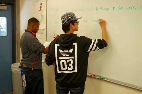 two students writing on the white board