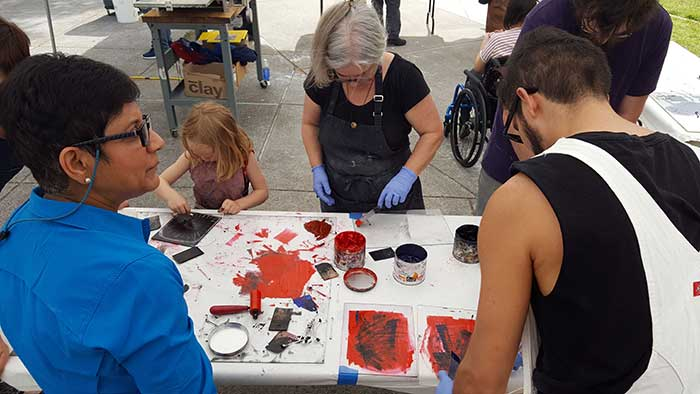 a crod of people using red paint while printmaking