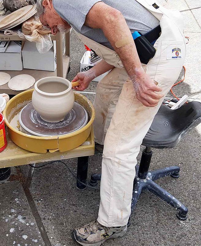 man working on pottery wheel