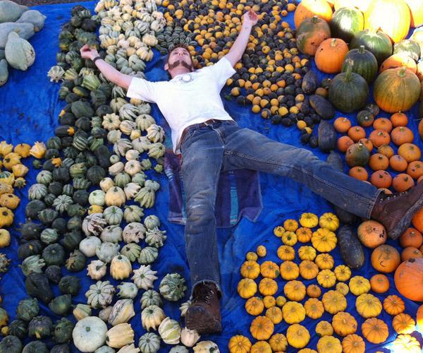 Man laying on ground among pumpkins on display