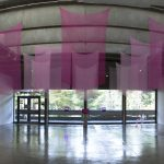 Panorama view of art gallery with sheer pink fabrics hanging from the ceiling in the center of the room; a large yellow board with writing in on the floor on the left; 2 pink paintings are on the left wall, 3 pink paintings are on the right wall; a pink video monitor and 2 pink lights are on the far wall in the center. In the background are large windows that reveal a view of the trees outside.