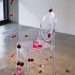 Detail of a larger sculpture; a clear plastic chair with a clear glass sitting on it; cherries are scattered on the floor and are hanging from the ceiling around and on top of the chair; there is a clear syrup dripped on the chair and floor.