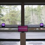 "View of art installation in gallery with a video monitor in the center with the words ""Pink is scary"" on it and a pink light on either side of the monitor. Behind the installation are large windows that show a view of the trees outside."