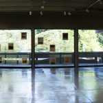 Panorama view of gallery with abstract photos on left and right sides, and in the middle the floor to ceiling windows with photos mounted on the glass and a view of trees outside.
