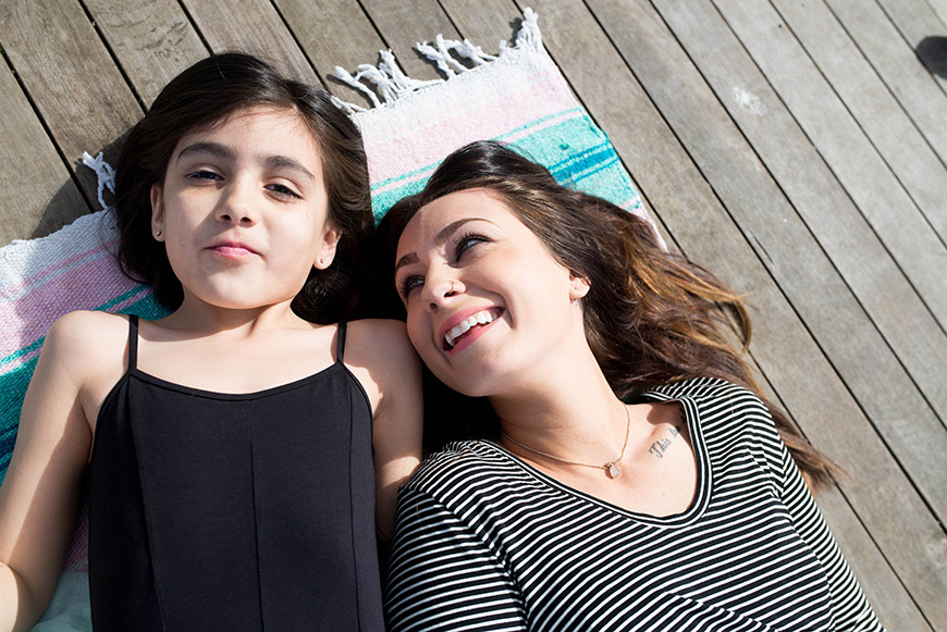 Woman and daughter laying on a blanket and smiling