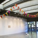 Gallery installation view of artwork made up of triangular flags attached to a ribbon and draped across the ceiling of the gallery; the flags are yellow, orange and pink, with various painted images on them. The gallery has other artworks throughout and in the background are large windows showing the trees outside.