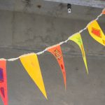 White ribbon with five triangular flags attached to it. The yellow, orange and pink flags have abstract images painted on them; the background is a concrete ceiling.