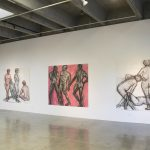 Four large scale drawings, each with three nude figures, drawn in charcoal and watercolor, hung on wall in gallery.